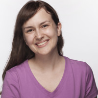 Portrait of smiling young woman in purple t-shirt, studio shot